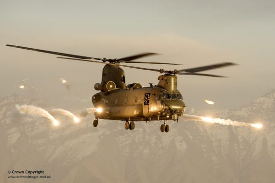 An RAF Chinook helicopter in silhouette, flying over Afghanistan. | by Defence Images