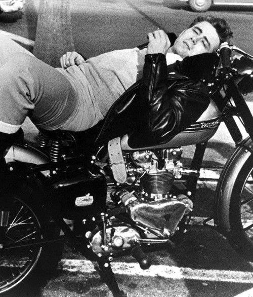 James Dean lounging on his Triumph in a classic leather motorcycle jacket.