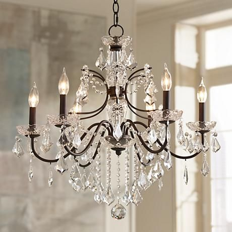 Adorned with a bronze finish and paired with clear crystals, this chandelier adds class and sophistication to any space.