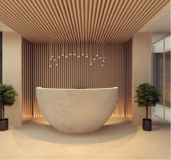 Beautiful round concrete reception desk, also love the timber cladding runs from wall to ceiling!!