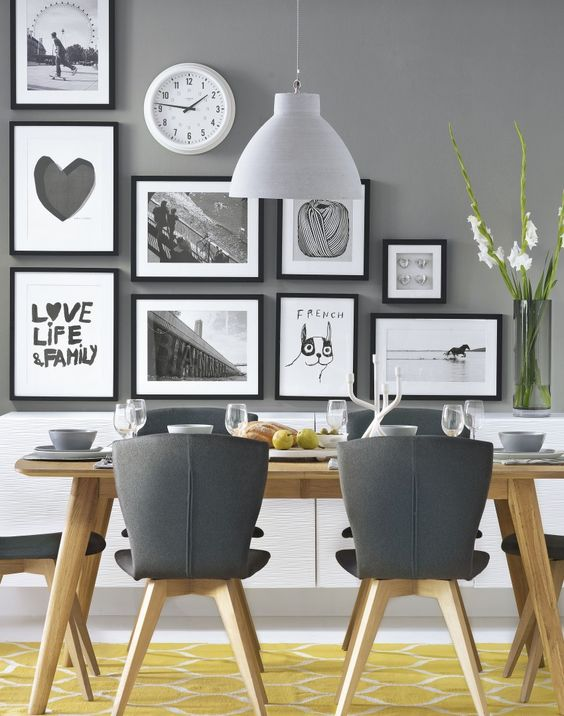 Dining room inspiration: We love this feature wall, with quirky prints featured on grey. The yellow geometric rug breaks up the colours and makes a statement! This modern dining room is a