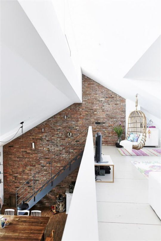 Frankfort, Germany | Built from a recycled barn, one entire side of the house is built from the old barn brick, each of which have been washed with a brush. Beams have been recycled as structural support for the mezzanine where there's a family room (with a lovely wicker swing!) and study. Love the stairs and the multi-angled ceiling as well.