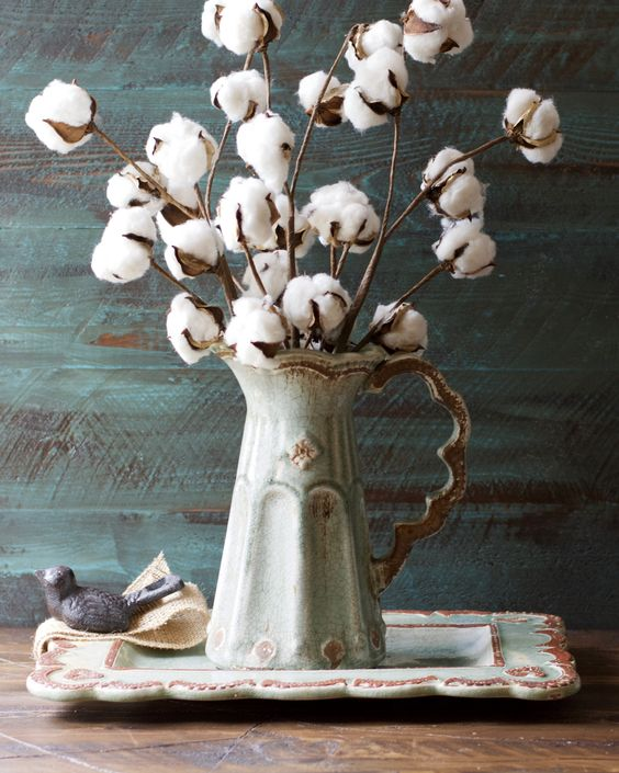 I love flowers and branches collected from your own yard used as a part of the decor, like these cotton bundles.