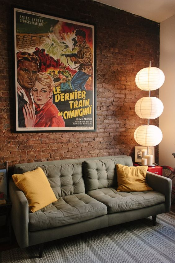 omg, these are a few of my favorite things, brick walls, dark couch, vintage poster and paper lamps!!!