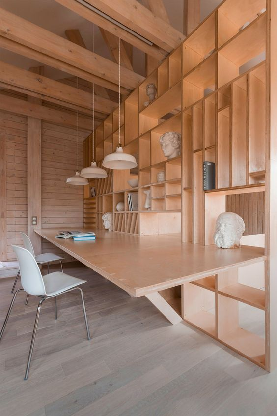 Plywood artist's studio by Ruetemple combines areas for storage, seating and sleeping.
