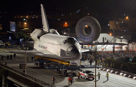 Space Shuttle Endeavour passing Randy's Donuts on the streets of Los Angeles