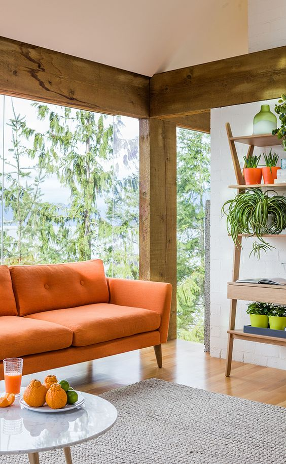 To unify a space dominated by a statement sofa like the EMIL in 'Papaya Orange', incorporate your accent color subtly throughout the room.