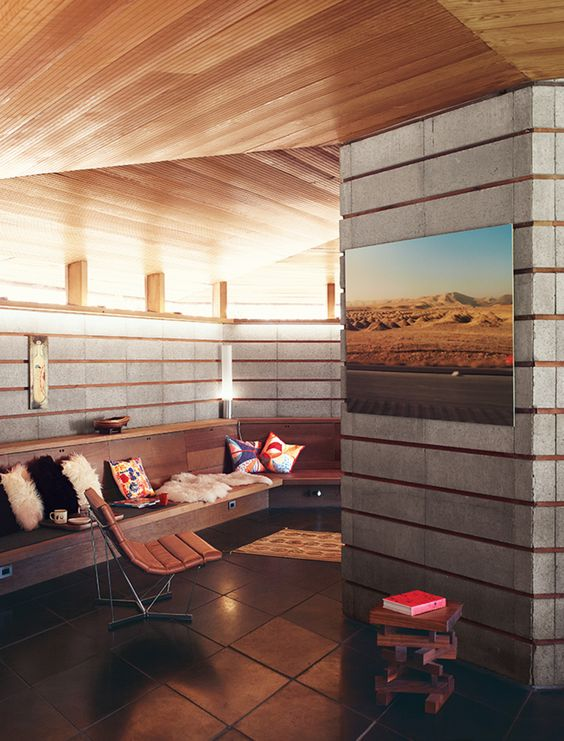 A concrete-block wall and a built-in bench line the living room, where a photo by Robbins and a painting by Barry McGee hang near a Catenary chair by George Nelson.