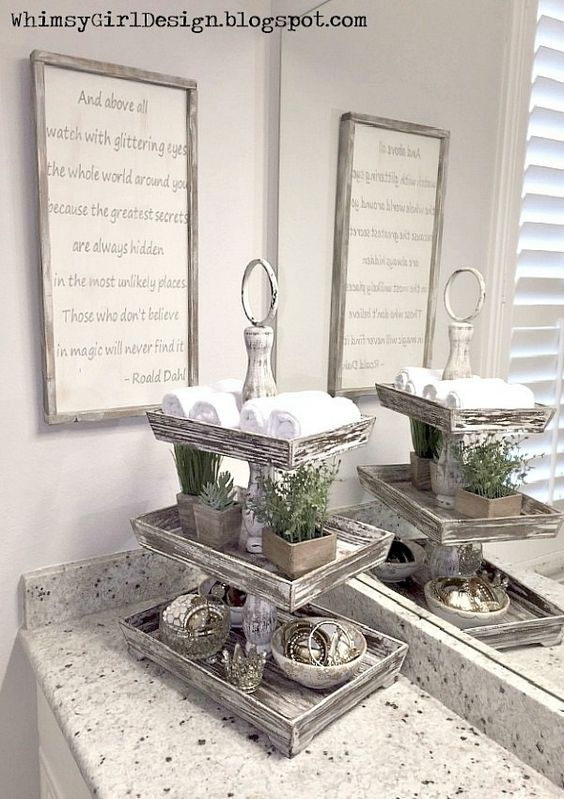 Here's a stylish way to add storage space to a bathroom vanity. This three-tiered stand holds hand towels and is also used for jewelry storage.