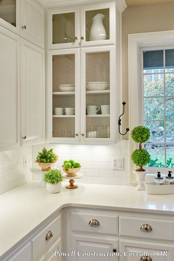 This classic white kitchen with fresh accents and open, glass louvered cabinets and subway tile backsplash is timeless. #WhiteCabinets #quartz #GlassCabinets #kitchen