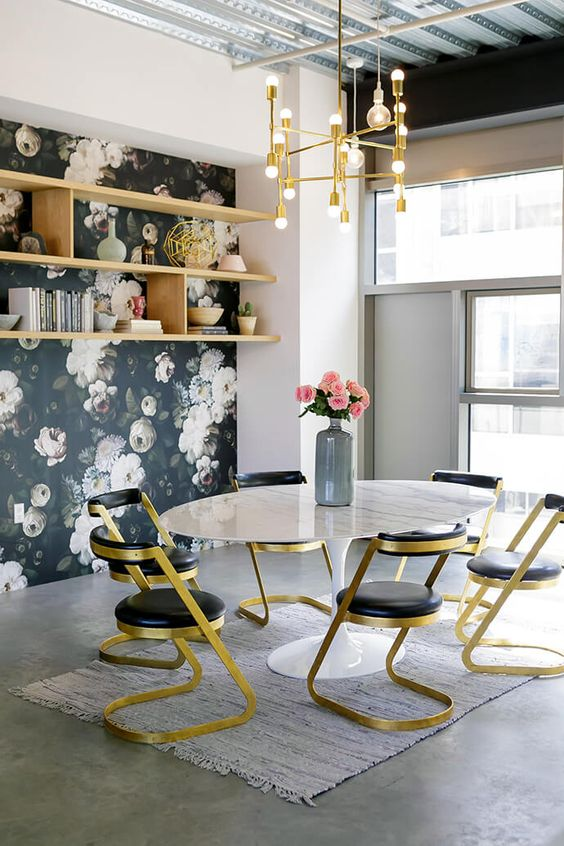 Feminine workspace with floral wallpaper, a gold chandelier and gold chairs