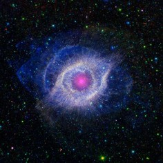 A dying star throws a cosmic tantrum in this combined image from Nasa's Spitzer Space Telescope and the Galaxy Evolution Explorer. The star's dusty outer layers are unraveling into space, glowing from the intense ultraviolet radiation being pumped out by the hot stellar core. This object, called the Helix nebula, lies 650 light years away in the constellation of Aquarius