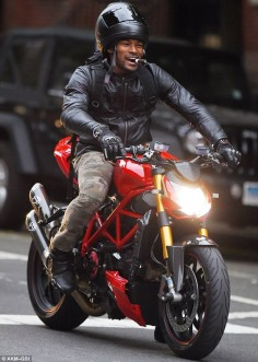 Born to be wild! Tyson Beckford, 43, was seen riding atop his motorbike while not completely wearing his helmet and smoking a cigar in the West Village neighbourhood of New York on Thursday