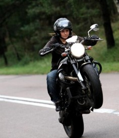 I just love the look on her face.  Yeh, no big deal. Lofting the wheel on a Moto Guzzi; just another day
