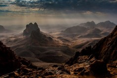 In this beautiful photograph by Brigitte Djajasasmita we see the Hoggar Mountains of Algeria. The Hoggar Mountains, also known as the Ahaggar, are a highland region in central Sahara, or southern Algeria, along the Tropic of Cancer. They are located about 1,500 km (900 mi) south of the capital, Algiers and just west of Tamanghasset.