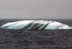 Some of the stripes formed when layers of the iceberg melted and refroze.  Others were created from the dust and soil picked up when the ice sheet that gave birth to the iceberg was sliding down an Antarctic hillside.