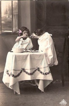 A little girl and her dog play tea party