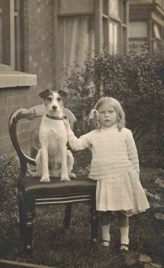 A little girl with her Jack Russell Terrier. Look how proud he is sitting on the chair