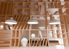 A plywood partition separates working and relaxation areas inside this Moscow studio and incorporates furniture and shelves for art supplies.