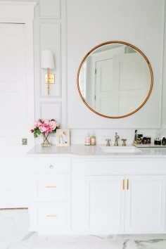 Brass mirror in a white bathroom