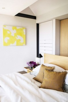 Comfy bedroom with bright yellow art, and a neutral color palette