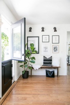 Entryway with a wood bench and black and white gallery wall