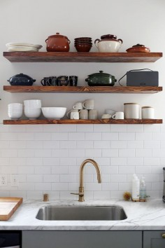 floating wood shelves with white subway tile and brass fixtures