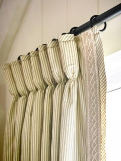 Goblet Pleated drapes embellished with a banded trim down the lead edge and the stripe cut on the bias at the top of the pleat and outside the banding. It's all in the details.