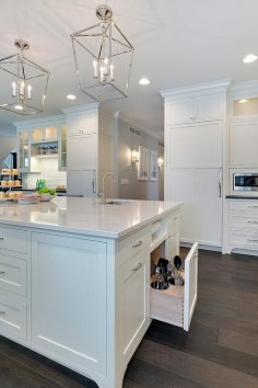Gorgeous kitchen island sat upon stained oak hardwood floors features white shaker cabinets topped with a white marble countertop fitted with a curved prep sink and polished nickel faucet illuminated by two 4 light Darlana lanterns and recessed lighting.