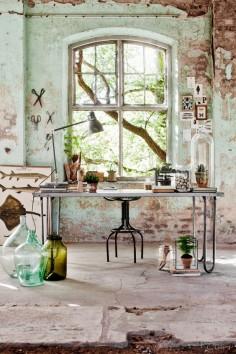 Le mobilier de bureau de style industriel est bien adapté au décor. De petites dames-jeannes et autres pots allègent le tout.