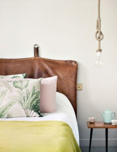 leather headboard with tropical colors and pillows in the bedroom, gorgeous combo!