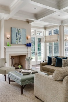 Living room with french doors, coffered ceilings, fireplace with herringbone tile, teal ottoman, beige couched | KL Interiors