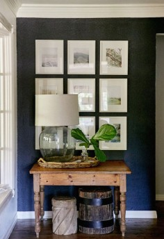 love this dark accent wall + the way the photos are displayed