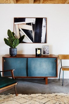 Mid-century modern sideboard underneath abstract art.