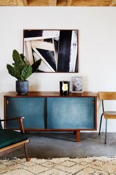 Mid-century modern sideboard underneath abstract art.