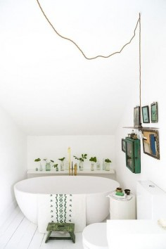 modern white bathroom with pops of green plants and art