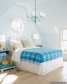 The key to enlivening a neutral room is to brighten it with several shades of the same color. In a mostly pale room, a plaid blanket makes a strong statement. The chandelier, the wall-mounted bedside tables, and the cushion on the dog bed reiterate the blanket's several shades of blue.