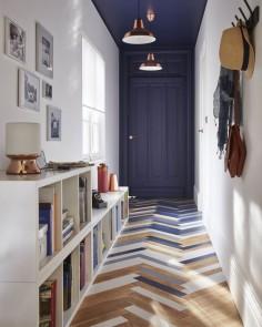 Un joli couloir / entrée, avec son parquet peint en tons de bleu ardoise et de blanc. Le bleu se répand aussi sur le mur du fond et le plafond, créant un intéressant effet de perspective.