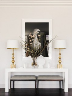 White and gold lamps on top of a white table with a glass vase and black and white wall art
