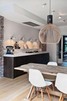 Witte eamnes eettafel stoelen met houten poten aan een steigerhouten tafel en bij de keuken zilveren industriële lampen