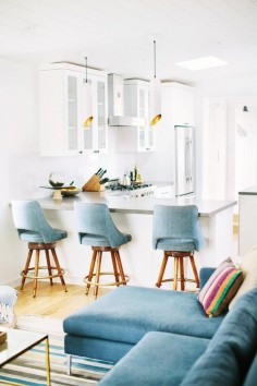 An open bright kitchen with vintage barstools, and pendant lights
