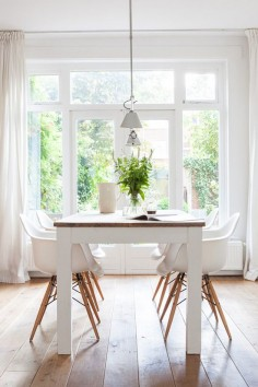 DSW Chairs, white and wood dining table, wide-planked flooring, full length windows and low over-table lights - pretty darn perfect