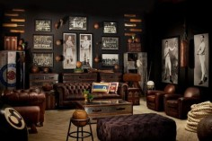 Restoration Hardware sports room/man cave with masculine elements. Brown leather chesterfield sofa, tufted leather ottoman, old world touches, and vintage prints and etchings. I really like the aluminum trunks and club chairs, but I'm not sold on the lockers or the giant 8-ball, which seem a bit gimmicky to me. This room would look even more amazing with a pair of orb chandeliers.