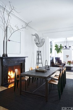 The dining table by Jerôme Abel Seguin is from Ralph Pucci, the vintage chairs are by Jean Prouvé, the photograph over the mantel is by Catherine Opie, the sculpture is by Elliott Hundley, and the vases on the mantel are by Rick Owens.