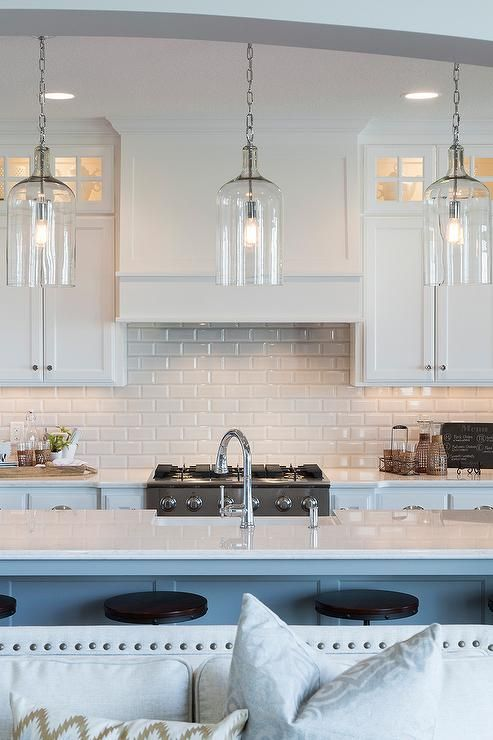 A trio of Corsica Pendants illuminate an extra long kitchen island topped with white quartz fitted ...