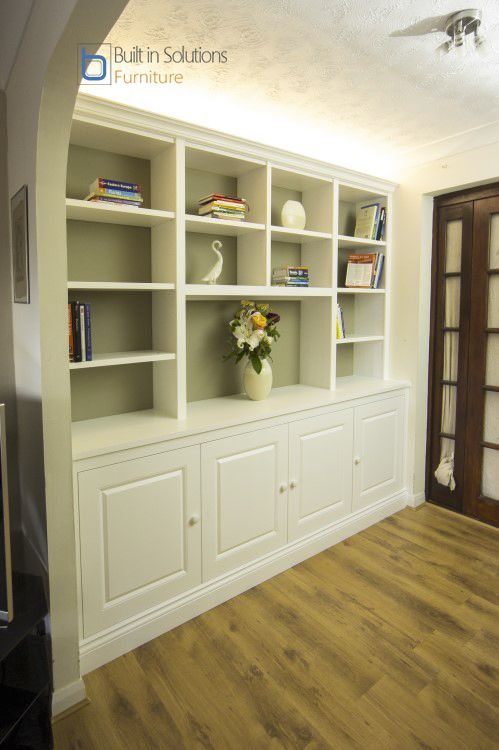 Built in Cabinets and shelving in a large alcove featuring raised panel doors and up lighting. The backing was painted in a darker color to add contrast.