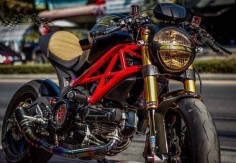 Black Ducati Monster with a custom seat, tinted headlights, clip-ons and Öhlins forks
