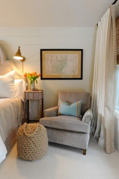 A cozy club chair adds warmth to a master bedroom. Chair on one side and small table.
