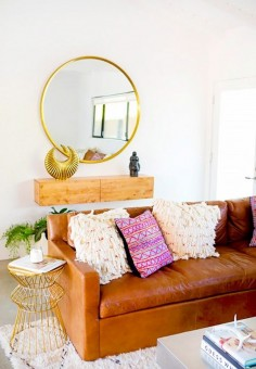 Bright boho living space with a leather sofa, a large rug, and a gold round mirror