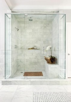 Chic master shower features ceiling and walls clad in marble brick tiles fitted with a marble shelf ledge finished with a marble pencil rail.